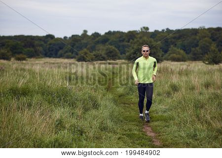 Fit muscular man jogging on a rural trail through grassland wearing sportswear and sunglasses in an active lifestyle concept