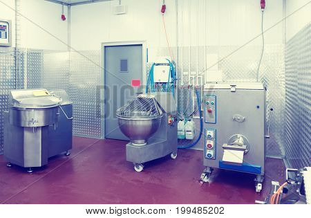 Professional meat processing equipment on food-making plant, toned image