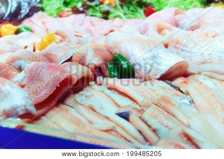Fish fillets on ice in big food product store, toned image