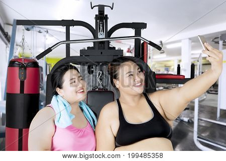 Two overweight women taking a selfie photo with a smartphone after exercise in the fitness center