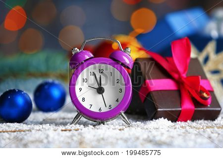 Retro alarm clock, decorations and gift box on table. Christmas countdown concept