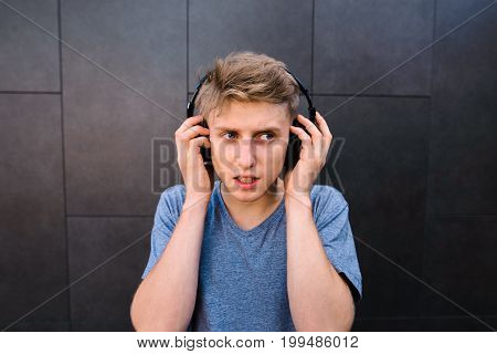 A concessionary young man listens to music in the headphones on the back of a gray wall. Emotional teenager in the headphones on the head looks to the side