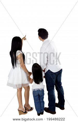 Back view of young parents pointing and looking at something while holding their hands daughter isolated on white background