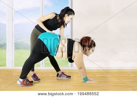 Image of young female instructor helps a beginner to exercise near a window