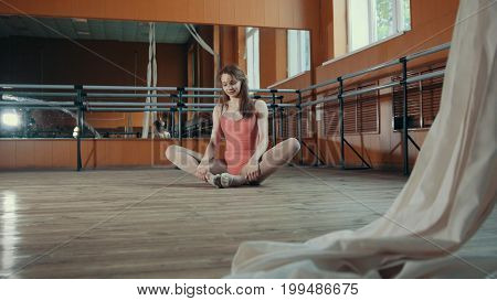 Model girl in pink dress and pointe shoes ballerina practicing in the studio, wide angle