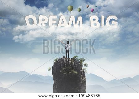 Back view of young male open his arms on the mountain peak while looking at text of dream big on the sky