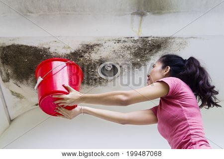 Photo of young woman holding a bucket while collecting drops rainwater from damaged ceiling