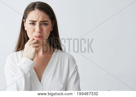 Portrait of nervous young brunette girl thinking looking at camera holding hand on chin over white background. Copy space.