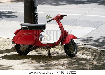 BERLIN, GERMANY - AUGUST 06, 2017: A red Vespa stands on the edge of the Kurfürstendamm in Berlin