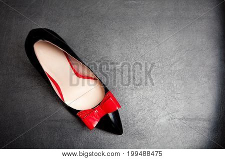 Patent-leather shoe with red bow on black leather background.