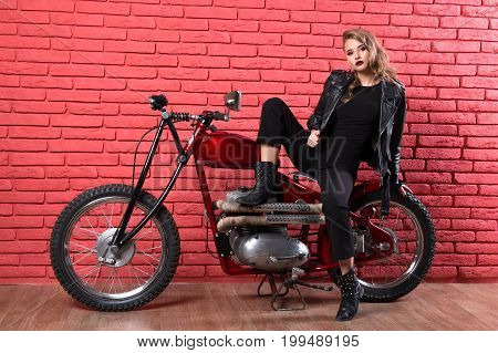 Coveted Woman Or Girl In A Leather Jacket And Tight Pants, Boots Sits On A Motorcycle, With An Unusu