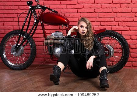 Coveted Woman Or Girl In A Leather Jacket And Tight Pants, Boots Sits Neer Motorcycle, With An Unusu