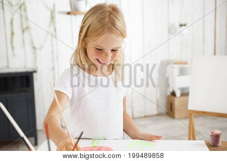 Smiling and cheerful, full of joy child with blonde hair and freckles holding brush in her hand and aspiringly painting picture at the art room. Shot of happy blonde little girl using watercolors, sitting at the desk with paper sheets, brushes and jar of