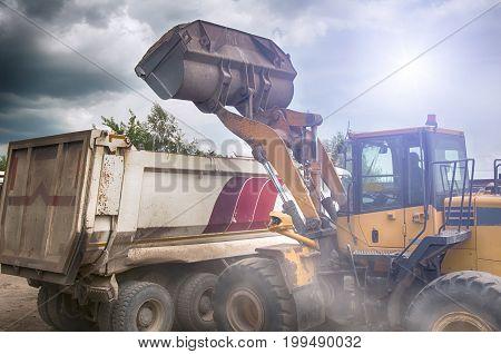 a excavator loads gravel in truck. A close up
