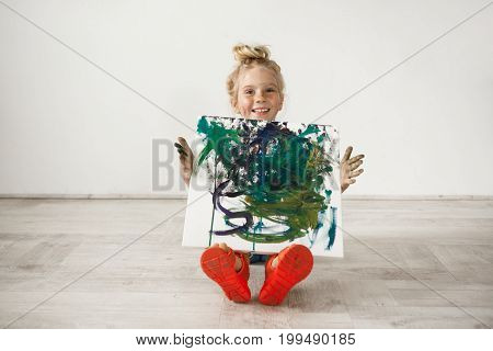 Indoor shot of blonde little girl with freckled face and hair bun looking at the camera, showing picture to her parents. Cute female child posing isolated at white wall.