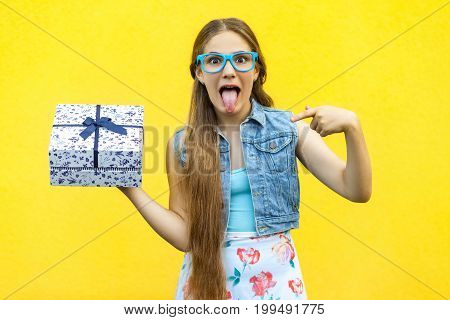 The funny blonde girl in dress and blue glasses tongue out at the camera pointing finger on present box isolated over yellow background. Indoor studio shoot