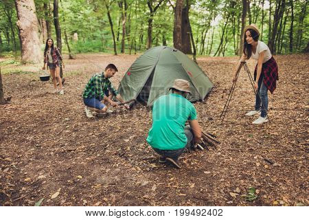 Trekking, Camping And Wild Life Concept. Photo Of Four Best Friends, Setting The Camp In The Woods N