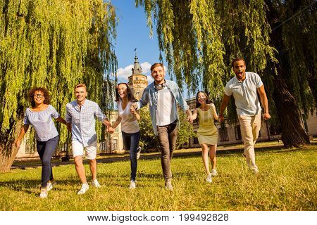 Freedom students friendship summer fun concept. Six happy international students are running in the park together holding hands wearing casual outfits sunny spring day