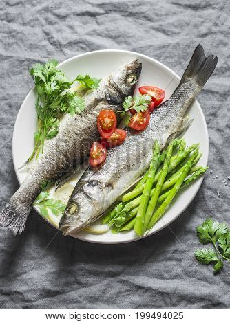 Baked sea bass with asparagus and tomatoes. Healthy diet food concept. On a gray background top view