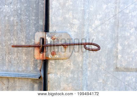 An old and rusted metal door latch.