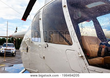 Nose of an orange colored helicopter parked on a concrete slab under blue skies.