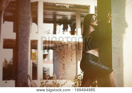 A Coveted Woman Or Girl Stands In The Middle Of An Abandoned Building In A Leather Skirt Top And Sun