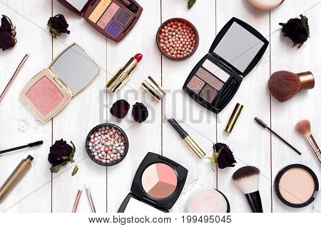 Various cosmetic products for make-up with a rose flower on a white wooden background top view. Decorative cosmetics female accessory makeup.
