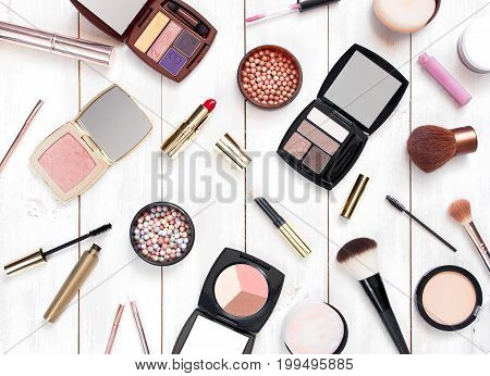 Various cosmetic products for make-up on a white wooden background top view. Decorative cosmetics female accessory makeup.
