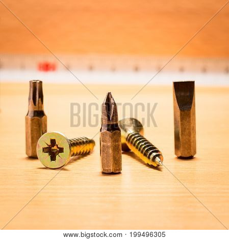 Three metal nozzles and two screws unfolded in different directions on a wooden background