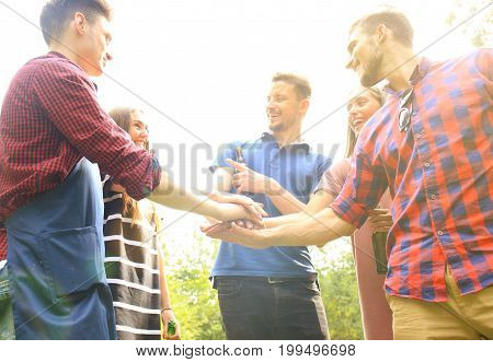 Friends join hand together during at barbecue in nature