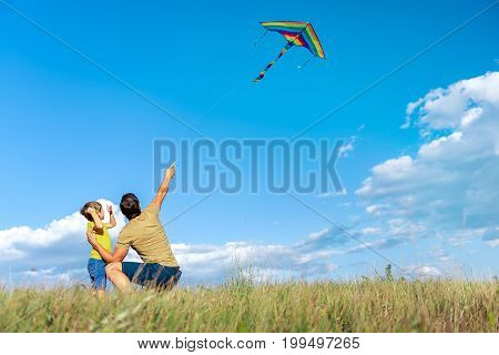 Look at this flying kite. Cheerful man is pointing finger to the sky while showing toy to his son. Boy is looking up with interest and laughing while standing on meadow