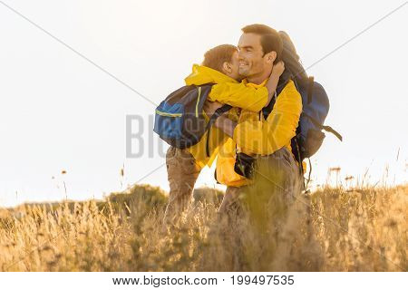My lovely daddy. Cute child is embracing father and kissing him with love. Man is kneeling on meadow and smiling. Family is carrying touristic backpacks