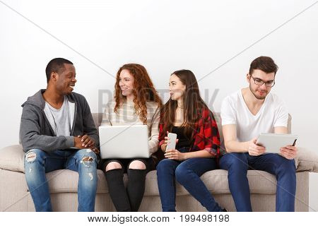 Multiethnic young students study with gadgets, preparing for exam, sitting on sofa in living room, studio shot