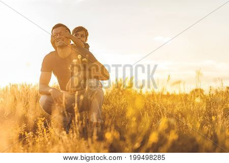 Cheerful boy is covering eyes secretly of his father while standing on meadow. Man is smiling with happiness. Copy space in right side