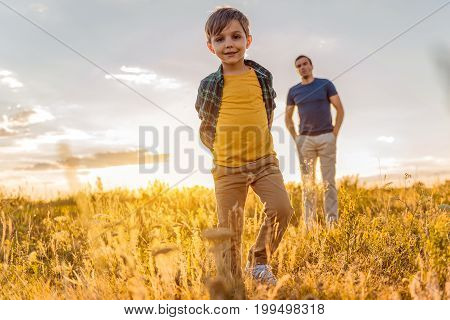 Low angle full length portrait of joyful boy playing on meadow. He is looking at camera and smiling. His father is standing behind him