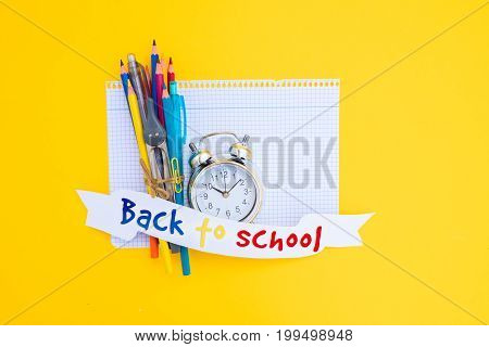 back to school concept - alarm clock and school supplies on ruled paper with back to school text on paper ribbon