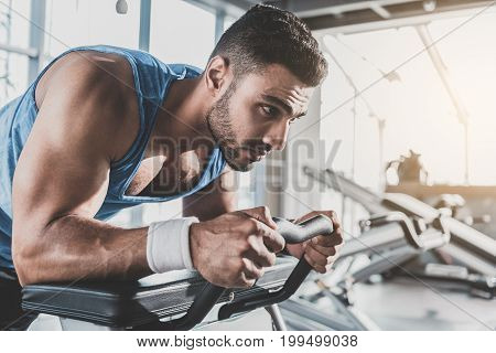 Side view bearded man expressing seriousness while engaging in sports activities in keep-fit studio
