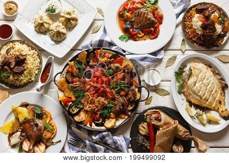 Presentation of variety georgian cuisine in restaurant. Stewed mutton and vegetables, grilled fish, khinkali, shawarma and other meat dishes with souce