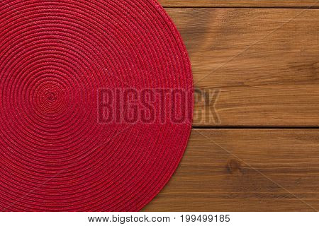 Background for plate - red wicker trivet on wooden table, top view, copy space