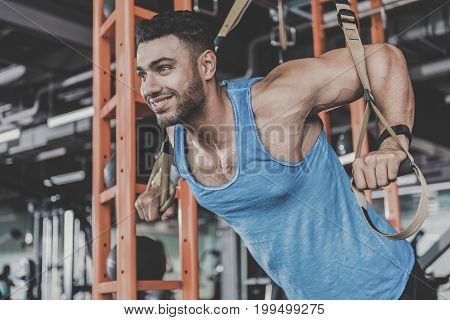 Low angle portrait of beaming young unshaven strong-arm man engaging in athletics with special tool in comfortable keep-fit studio