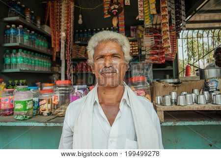 BELUR, INDIA - FEB 23, 2017: Portrait of indian man standing past rural store with food and water on February 23, 2017. Population of Karnataka state is 62000000 people