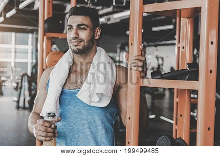 Portrait of man expressing gladness. He tasting beverage after good workout in keep-fit studio. Sport concept. Copy space