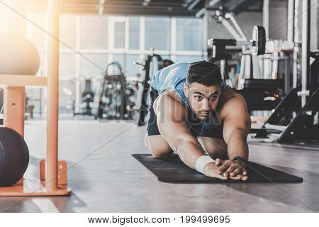 Portrait of bearded athlete expressing seriousness while taking physical exercise on mat in modern health club. Copy space