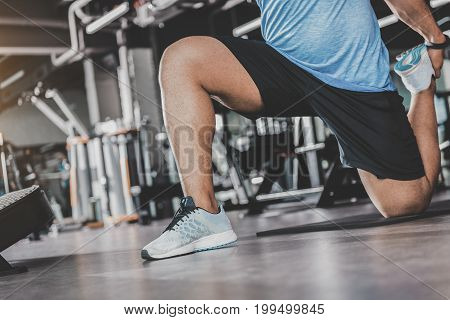 Close up legs of young athlete taking physical exercise in modern keep-fit studio. He wearing in sneakers. Low angle