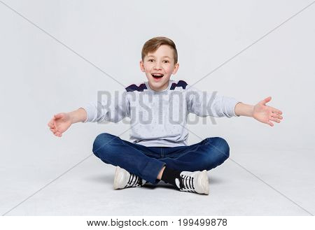 Ready to hug the world. Happy boy in braces sitting legs crossed on studio floor. Kid in casual laughing, posing on camera at white background, copy space