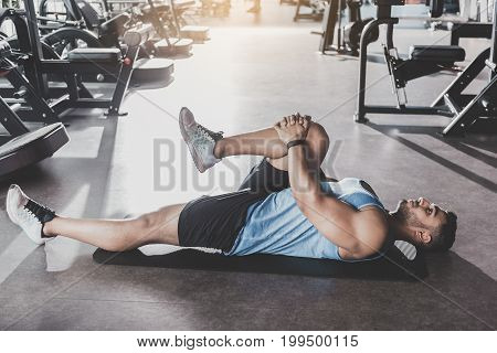 Full length side view serene unshaven strong-arm man lying in keep-fit studio. He taking exercise