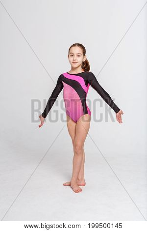 Little girl gymnast in leotard at white studio background. Sporty child in third ballet position of feet posing on camera. Healthy and active childhood concept, vertical, copy space