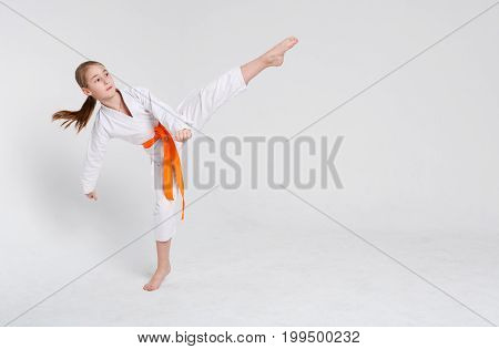 Karate girl at white studio background. Sporty teenager in kimono doing kick. practicing martial arts. Healthy lifestyle, active childhood and self defense concept, copy space