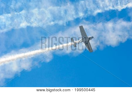 White Turboprop Airplane With A Trace Of White Smoke Against A Blue Sky