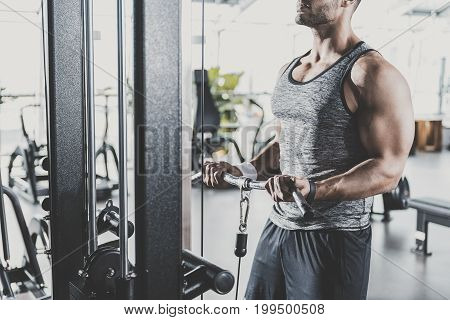 Male arms working out with equipment in modern keep-fit studio. He standing near it